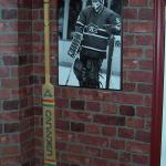 Ken Dryden goalie stick hung on a brick wall.